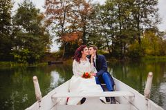 Couple newlyweds in the white boat. Beautiful couple newlyweds in the white boat at the background of autumn nature Royalty Free Stock Photos