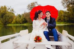 Couple newlyweds in the white boat. Beautiful couple newlyweds in the white boat with big red umbrella Royalty Free Stock Photo