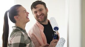Beautiful couple paint the walls in a new apartment, laughing and having fun. Young family makes repairs in their new