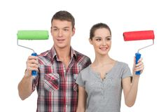 Beautiful couple painting white wall. Royalty Free Stock Images