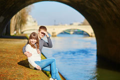 Beautiful couple in Paris walking by the Seine Stock Photos