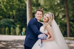 Beautiful couple in a Park. On a Sunny canopy at his wedding Stock Photos