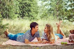 Beautiful couple on picnic, look at each other. Stock Image