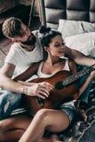Beautiful couple playing guitar. Royalty Free Stock Photos