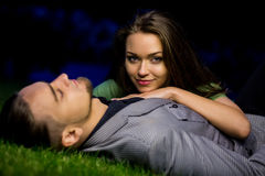 Beautiful couple posing on the grass. She leaned on him. Man closed his eyes and dreaming. Engagement in nature Royalty Free Stock Photography