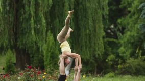 Beautiful couple practicing acro yoga. Young yoga instructors practice in a city park on green grass. Two successful stock video footage