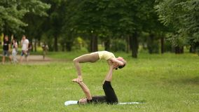Beautiful couple practicing acro yoga. Young yoga instructors practice in a city park on green grass. Two successful stock footage