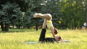 Beautiful couple practicing acro yoga. Young yoga instructors practice in a city park on green grass. Two successful stock video
