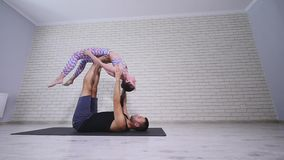 Beautiful couple practicing acro yoga. Young yoga instructors practice in a studio. Two successful young people perform stock video