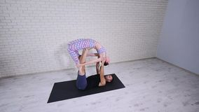 Beautiful couple practicing acro yoga. Young yoga instructors practice in a studio. Two successful young people perform stock video footage