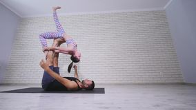 Beautiful couple practicing acro yoga. Young yoga instructors practice in a studio. Two successful young people perform stock footage