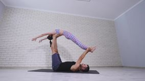 Beautiful couple practicing acro yoga. Young yoga instructors practice in a studio. Two successful young people perform. Acro yoga exercises Royalty Free Stock Photography