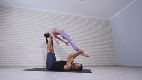 Beautiful couple practicing acro yoga. Young yoga instructors practice in a studio. Two successful young people perform. Acro yoga exercises Stock Images