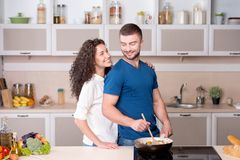 Beautiful couple preparing supper and looking at Stock Photos