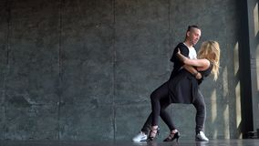 Beautiful couple of professional artists dancing passionate dance. Young couple dancing zouk dance