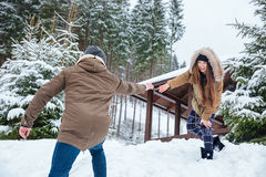 Beautiful couple reaching hands and helping each other in winter Stock Photo