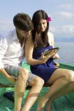 Beautiful couple reading ipad on lake in vacation Stock Images