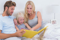 Beautiful couple reading a story to daughter Royalty Free Stock Photos