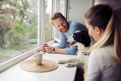 Beautiful couple relaxing at home and loving their dog Stock Photos
