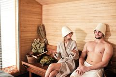 Beautiful couple relaxing in sauna and caring about health and skin. Young couple of tourist relaxing in a sauna sitting on wooden beach with bath bowls and stock images