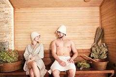 Beautiful couple relaxing in sauna and caring about health and skin. Young couple of tourist relaxing in a sauna sitting on wooden beach with bath bowls and royalty free stock photos