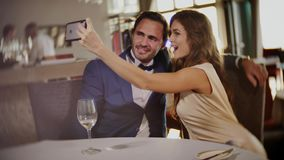 Beautiful couple taking selfie in a restaurant stock video footage
