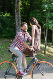 Beautiful couple riding a city bike and smiling to each other Stock Images