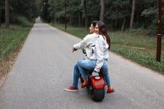 Beautiful couple riding an electric bike in a forest on the road. Beautiful couple riding an electric bike in a forest on the road stock photography