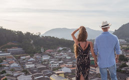 Beautiful couple on the roof. Back view of romantic couple holding hands while standing on top of skyscraper and admiring the cityscape at sunrise/sunset Stock Photos