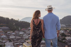 Beautiful couple on the roof. Back view of romantic couple holding hands while standing on top of skyscraper and admiring the cityscape at sunrise/sunset Royalty Free Stock Image