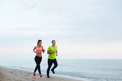 Beautiful couple running on the beach on a warm evening Royalty Free Stock Photos