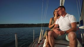 Beautiful couple is sailing river together in summertime.