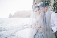 Beautiful couple on the seafront closed in a veil, laughing, smiling, happy, Wedding day, love royalty free stock images
