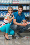 Beautiful Couple Showing Thumbs Up Sign In Supermarket. Beautiful Young Couple Showing Thumbs Up Sign In Supermarket Shopping For Milk And Cheese In Produce Stock Photo
