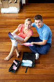 Beautiful couple sits on the floor picking colors Royalty Free Stock Photography