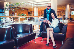 Beautiful couple sits in the hall of the hotel royalty free stock photography