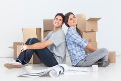 Beautiful couple sitting back to back. In their new house Stock Image