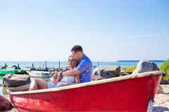 Beautiful couple sitting in boat on summer beach Stock Photos
