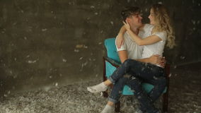 Beautiful couple sitting on a chair in the studio kissing stock footage