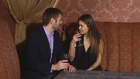 Beautiful couple sitting in a fancy restaurant and talking stock video footage