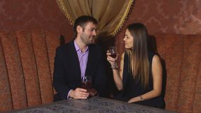 Beautiful couple sitting in a fancy restaurant and talking. A couple celebrates stock video