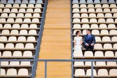 Beautiful couple sitting on football stadium stand Stock Image