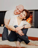 Beautiful couple sitting on fur carpet near fireplace Stock Photography