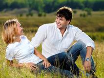 Beautiful couple sitting in meadow Stock Photo