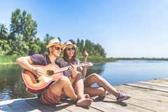 Beautiful couple sitting on pier with acoustic guitar and singing song. Love, music and nature concepts. Young fashionable couple playing acoustic guitar while royalty free stock photos