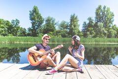 Young fashionable couple playing acoustic guitar while sitting on wooden dock against beautiful lake and trees. Summer concept. Beautiful couple sitting on pier royalty free stock photos