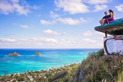 Young beautiful couple sitting on pillbox over looking Lanikai i. Beautiful couple sitting on pillbox over looking Lanikai in Kailua Hawaii royalty free stock photos