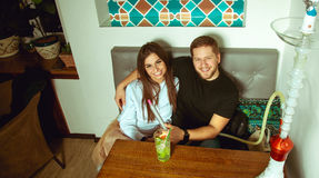 Beautiful couple sitting at a table in a cafe royalty free stock photography