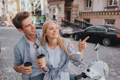 Beautiful couple is sitting together on motorcycle anf looking at each other. They are holding cups of coffee in hands Stock Photo