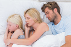Beautiful couple sleeping with daughter Stock Image